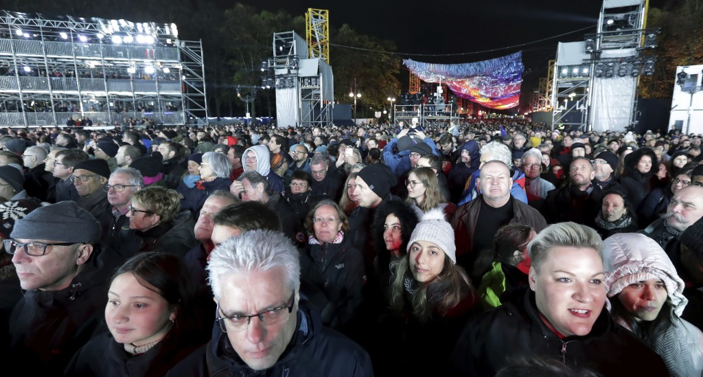 Visitors stay in front of the Brandenburg Gate as they attend stage presentations to celebrate the 30th anniversary of the fall of the Berlin Wall in ...