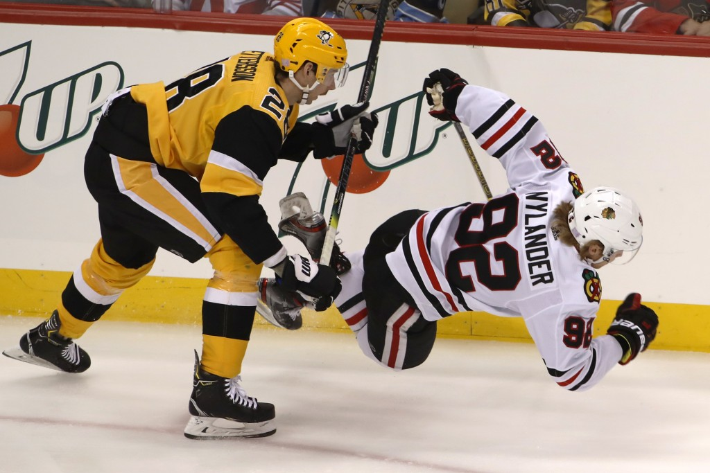 Pittsburgh Penguins' Marcus Pettersson (28) checks Chicago Blackhawks' Alex Nylander (92) off the puck during the first period of an NHL hockey game i...