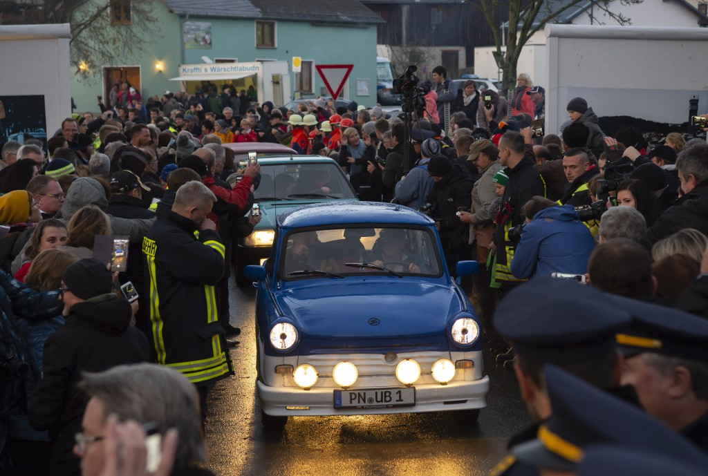 People welcome the legendary GDR Trabant (Trabi) cars, during a symbolic wall opening, celebrating the 30th anniversary of the falling wall in the out...