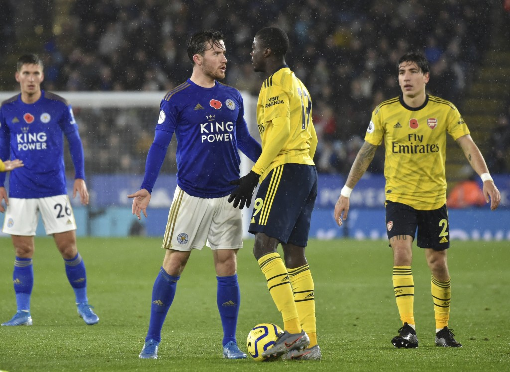 Arsenal's Nicolas Pepe, centre right, and Leicester's Ben Chilwell clash during the English Premier League soccer match between Leicester City and Ars...