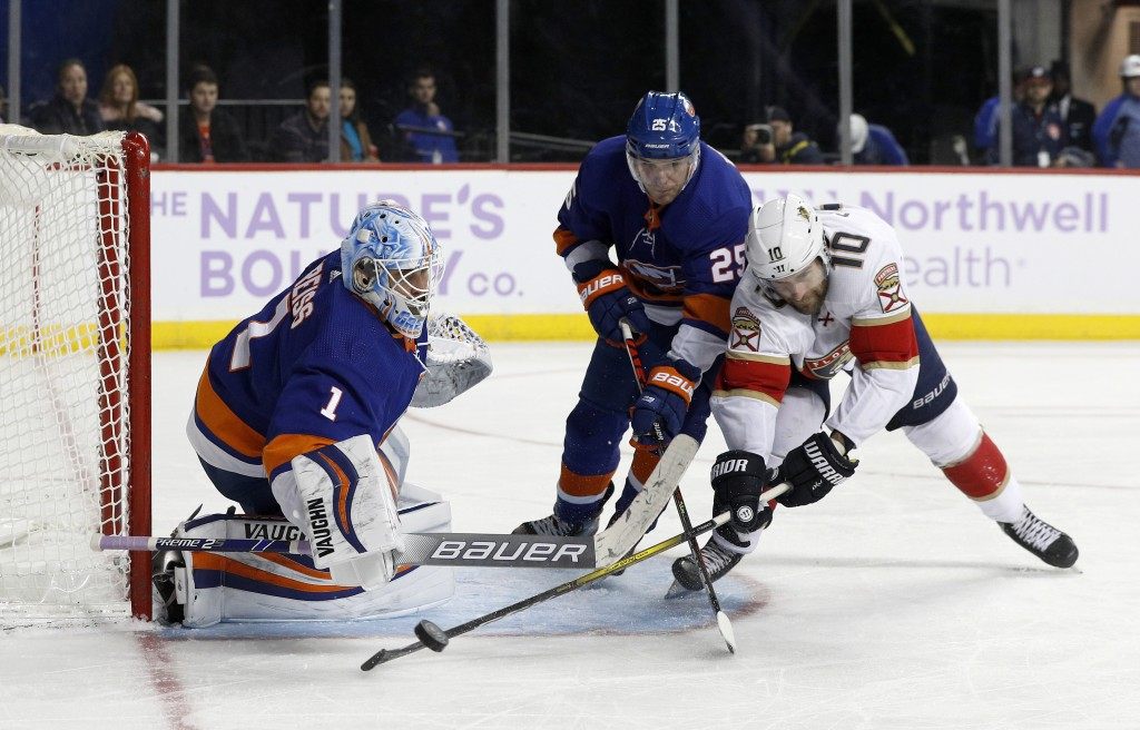 New York Islanders goaltender Thomas Greiss (1) and defenseman Devon Toews (25) stop a scoring chance against Florida Panthers right wing Brett Connol...