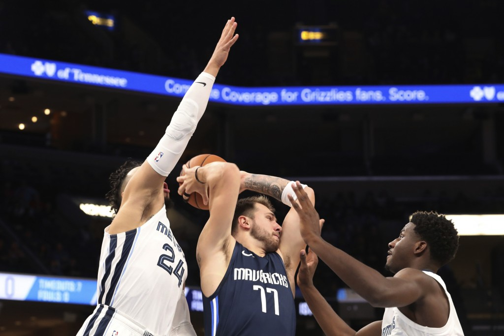 Memphis Grizzlies' Dillon Brooks (24) and Jaren Jackson Jr. (13) close in on Dallas Mavericks' Luka Doncic (77) during the first half of an NBA basket...