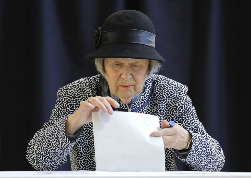 A woman casts her vote in Bucharest, Romania, Sunday, Nov. 10, 2019. Voting got underway in Romania's presidential election after a lackluster campaig...