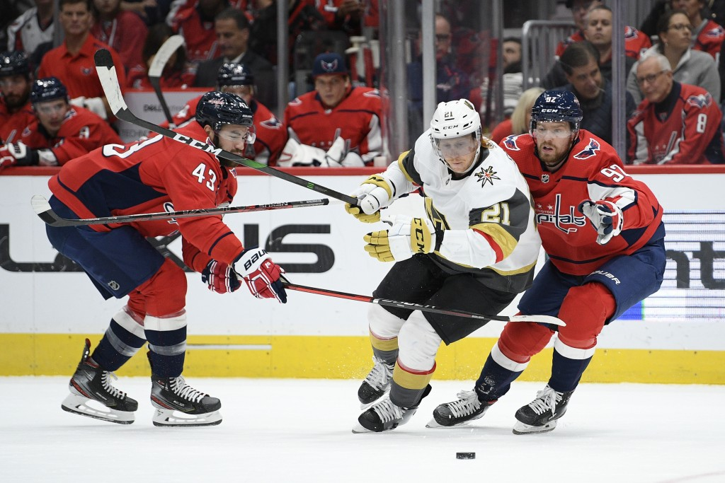 Vegas Golden Knights center Cody Eakin (21) battles for the puck against Washington Capitals right wing Tom Wilson (43) and center Evgeny Kuznetsov (9...