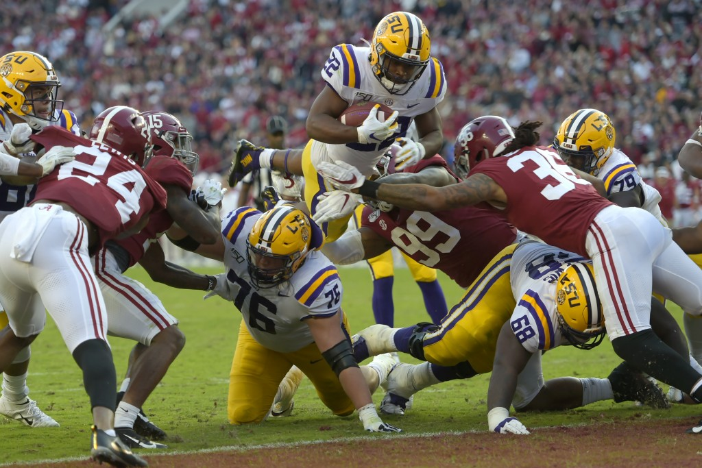 LSU running back Clyde Edwards-Helaire (22) dives over Alabama's Raekwon Davis (99) and Markail Benton (36) to score a touchdown in the first half of ...