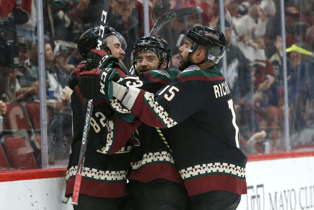 Arizona Coyotes center Vinnie Hinostroza, center, celebrates with Jordan Oesterle (82) and Brad Richardson (15) in the second period during an NHL hoc...