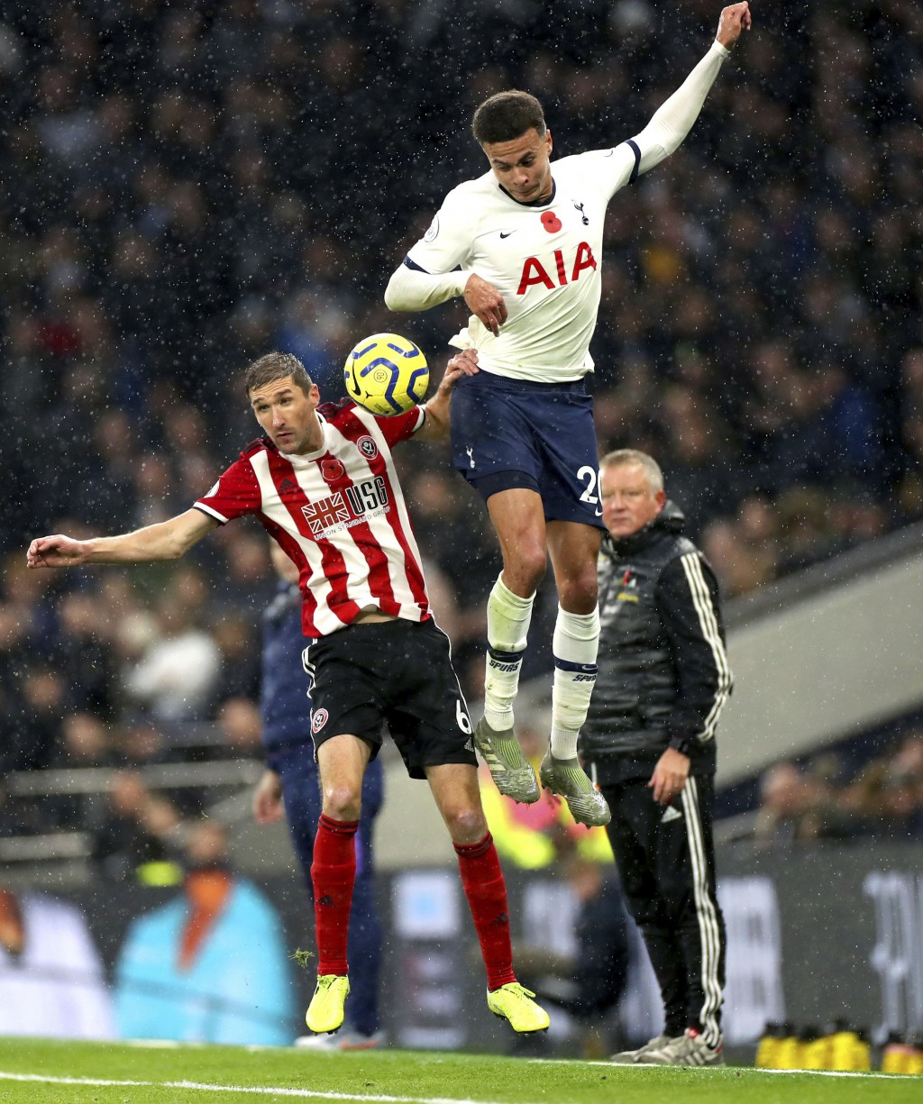 Sheffield United's Chris Basham, left and Tottenham Hotspur's Dele Alli battle for the ball, during the English Premier League soccer match between To...