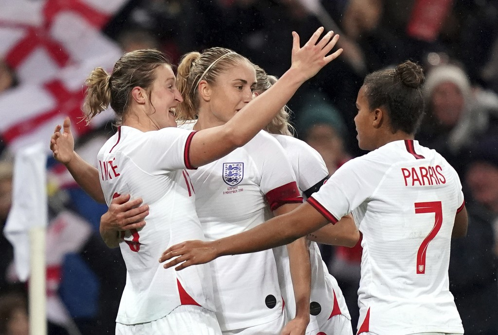 England's Ellen White, left, celebrates scoring her side's first goal with teammates, during the Women's International Friendly soccer match between E...