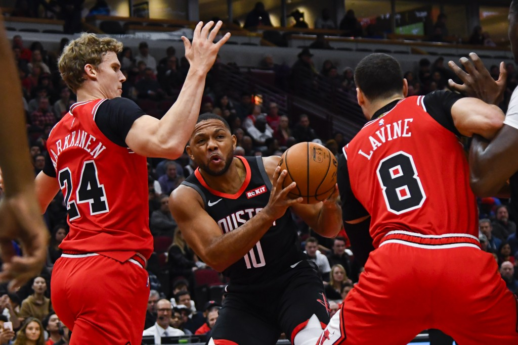 Houston Rockets guard Eric Gordon (10) drives to the basket between Chicago Bulls forward Lauri Markkanen (24) and guard Zach LaVine (8) during the fi...