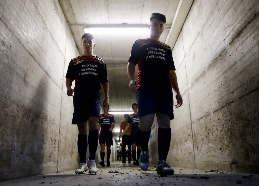 "Desio soccer players walk in the tunnel leading to the pitch with their faces painted with black marks and wearing jerseys reading "" The only race I k..."