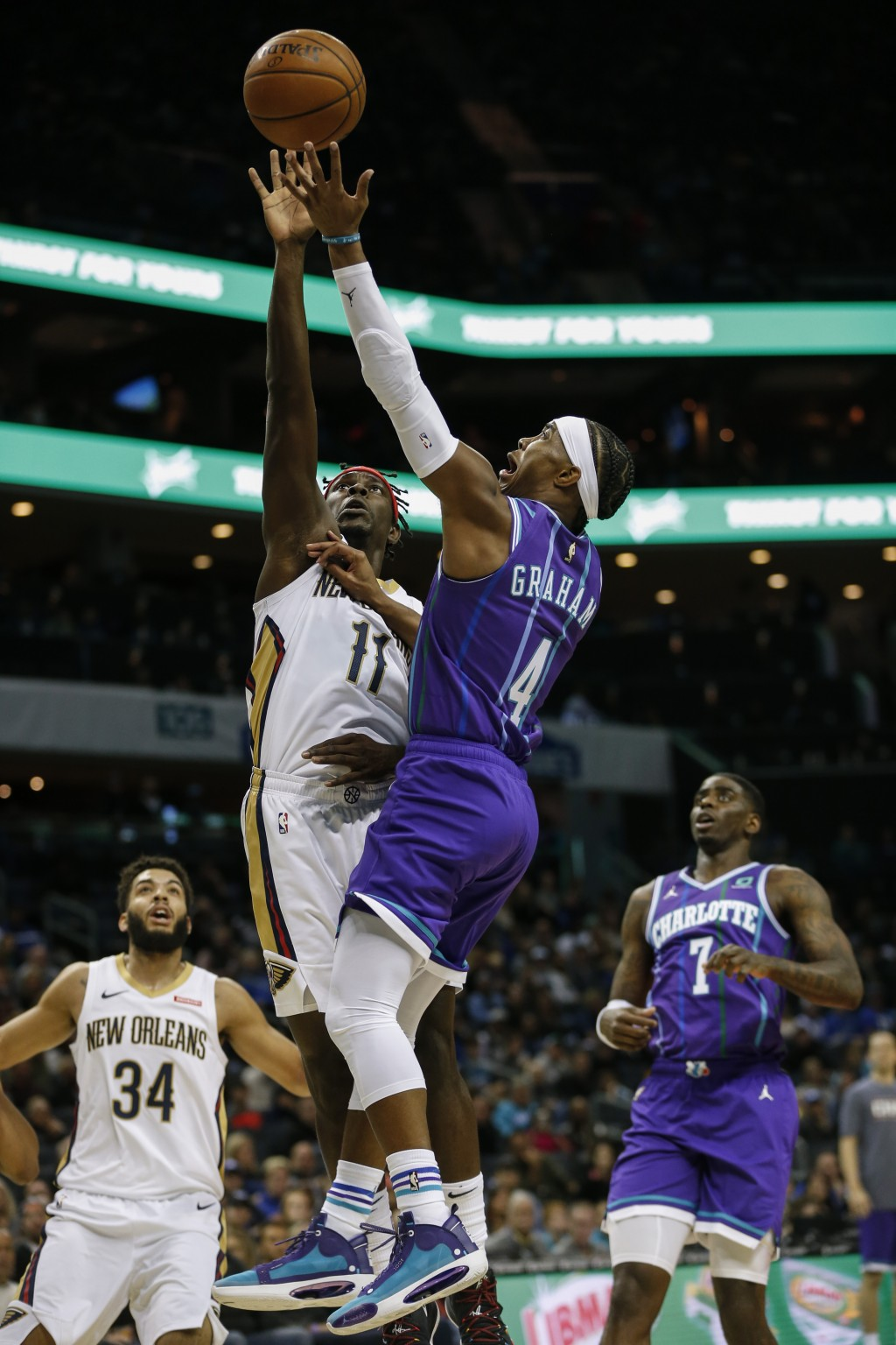 Charlotte Hornets guard Devonte' Graham (4) shoots over New Orleans Pelicans guard Jrue Holiday (11) as New Orleans Pelicans guard Kenrich Williams, l...