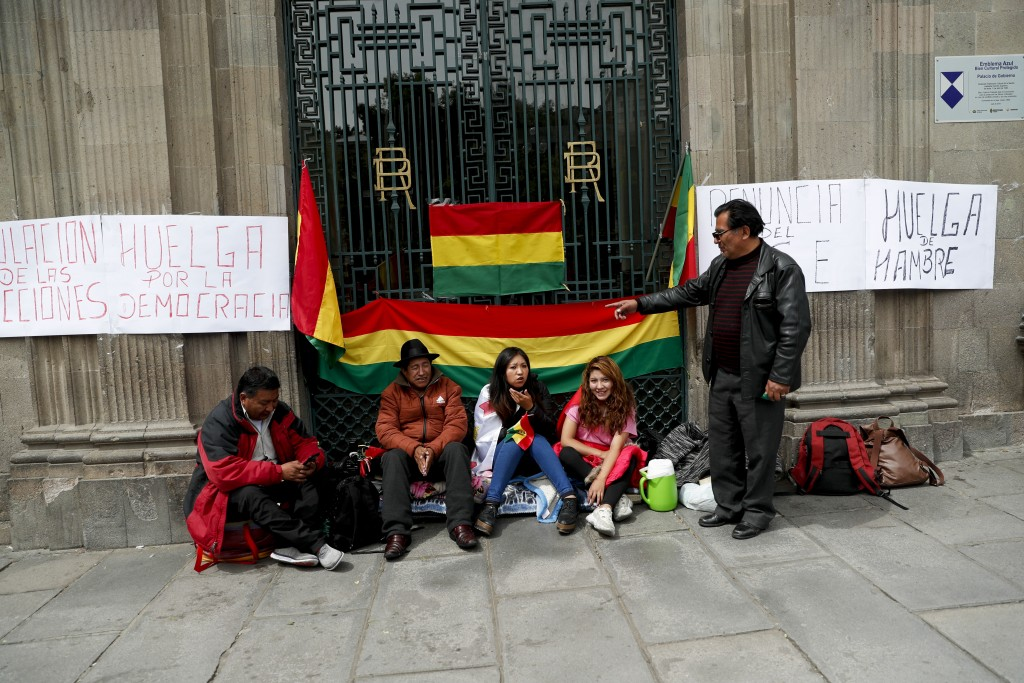 "Anti-government protesters sit outside the presidential palace as a banner in the wall reads in Spanish "" Annulment of elections, strike for democracy..."