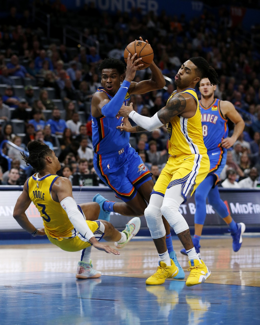 Oklahoma City Thunder's Shai Gilgeous-Alexander (2) goes against Golden State Warriors' Jordan Poole (3) and D'Angelo Russell (0) as Danilo Gallinari ...