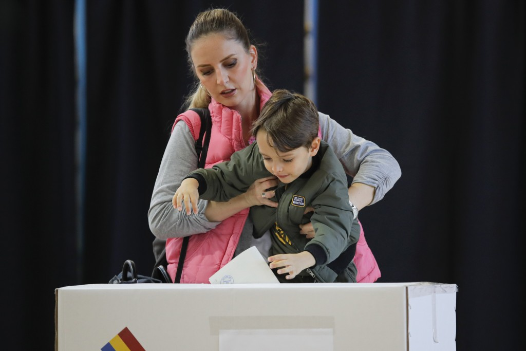 A woman holds a child to cast her vote in Bucharest, Romania, Sunday, Nov. 10, 2019. Voting got underway in Romania's presidential election after a la...