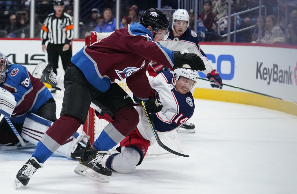 Colorado Avalanche defenseman Cale Makar (8) knocks over Columbus Blue Jackets center Gustav Nyquist (14) during the first period of an NHL hockey gam...