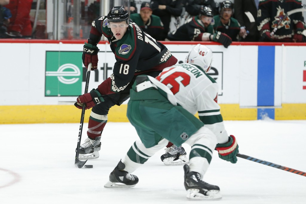 Arizona Coyotes left wing Christian Dvorak (18) carries the puck in front of Minnesota Wild left wing Jason Zucker in the second period during an NHL ...
