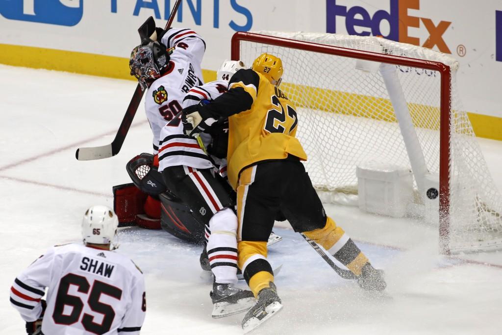 Pittsburgh Penguins' Nick Bjugstad (27) hits the goalpost behind Chicago Blackhawks goaltender Corey Crawford (50) with Blackhawks' Calvin de Haan (44...