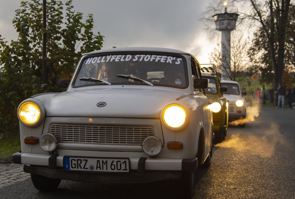 Legendary GDR Trabant (Trabi) cars,drive in front of a control tower of the former GDR border guard forces  during a symbolic wall opening, celebratin...