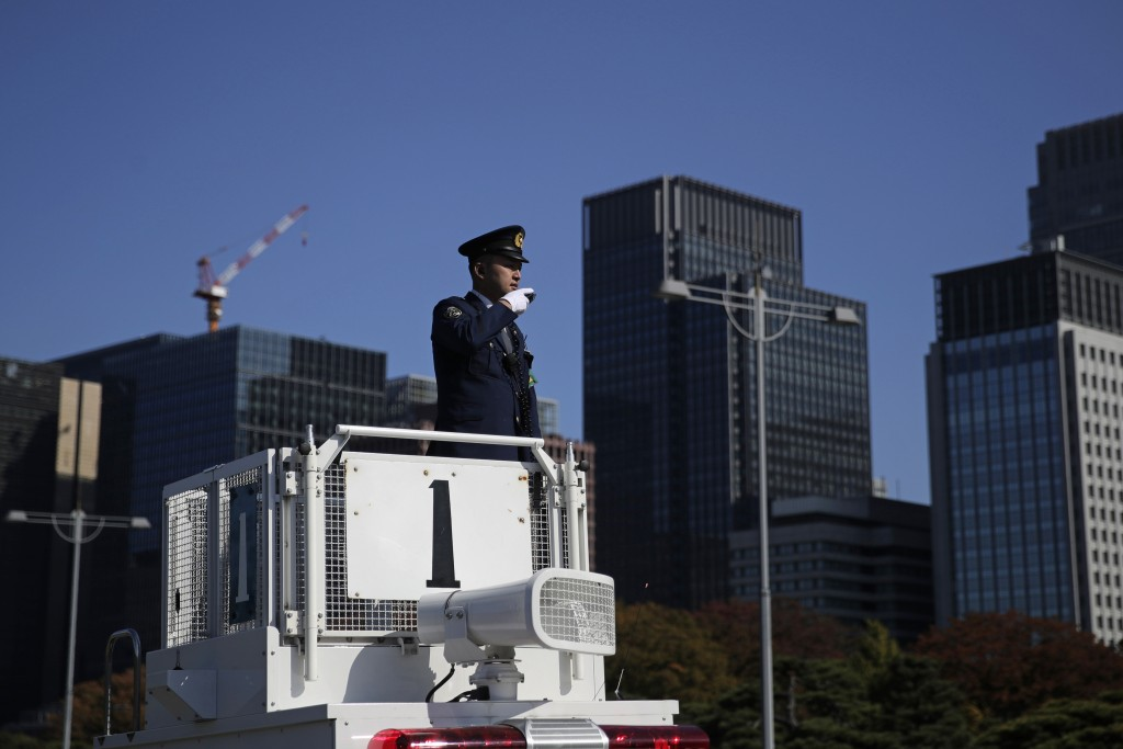 A police officer stands guard outside the Imperial Palace before the royal parade of Japanese Emperor Naruhito and Empress Masako in Tokyo, Sunday, No...