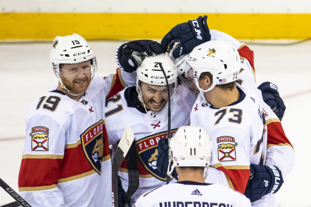 Florida Panthers defenseman Mike Matheson (19) and left wing Dryden Hunt (73) celebrate with center Vincent Trocheck (21) after he scored during the s...