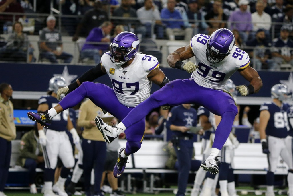 Minnesota Vikings' Everson Griffen (97) and Danielle Hunter (99) celebrate a sack of Dallas Cowboys' Dak Prescott during the second half of an NFL foo...