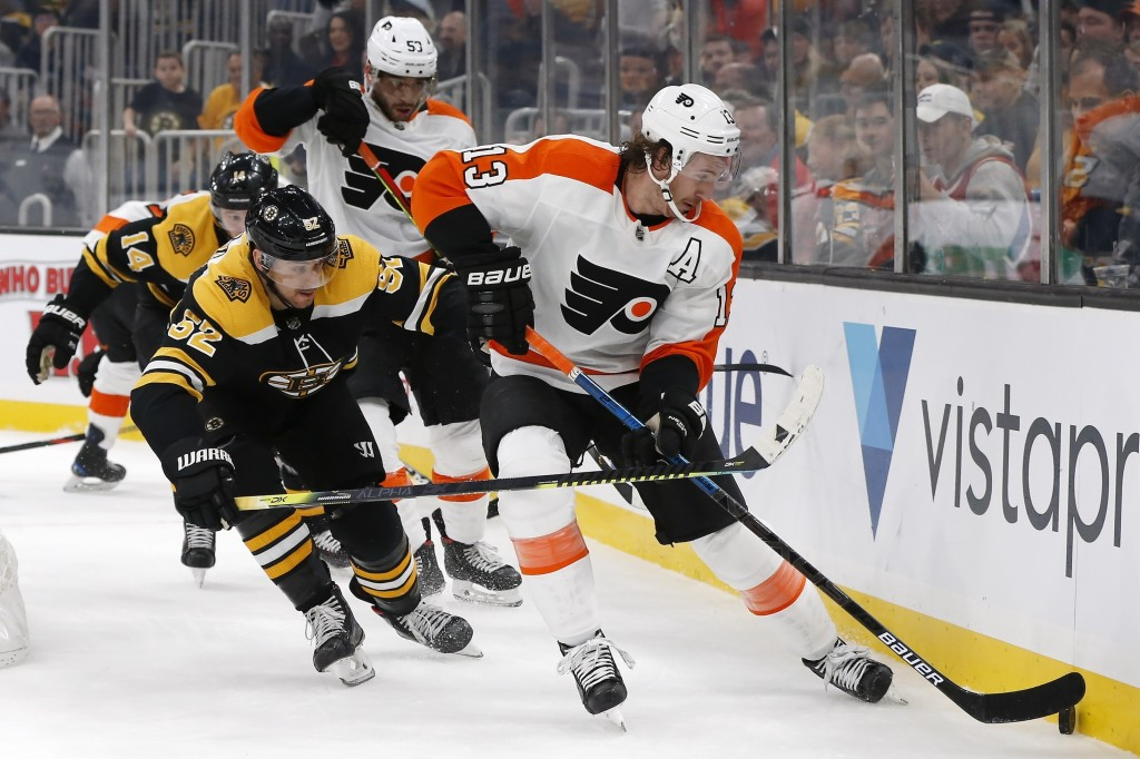 Boston Bruins' Sean Kuraly (52) battles Philadelphia Flyers' Kevin Hayes (13) for the puck during the first period of an NHL hockey game in Boston, Su...