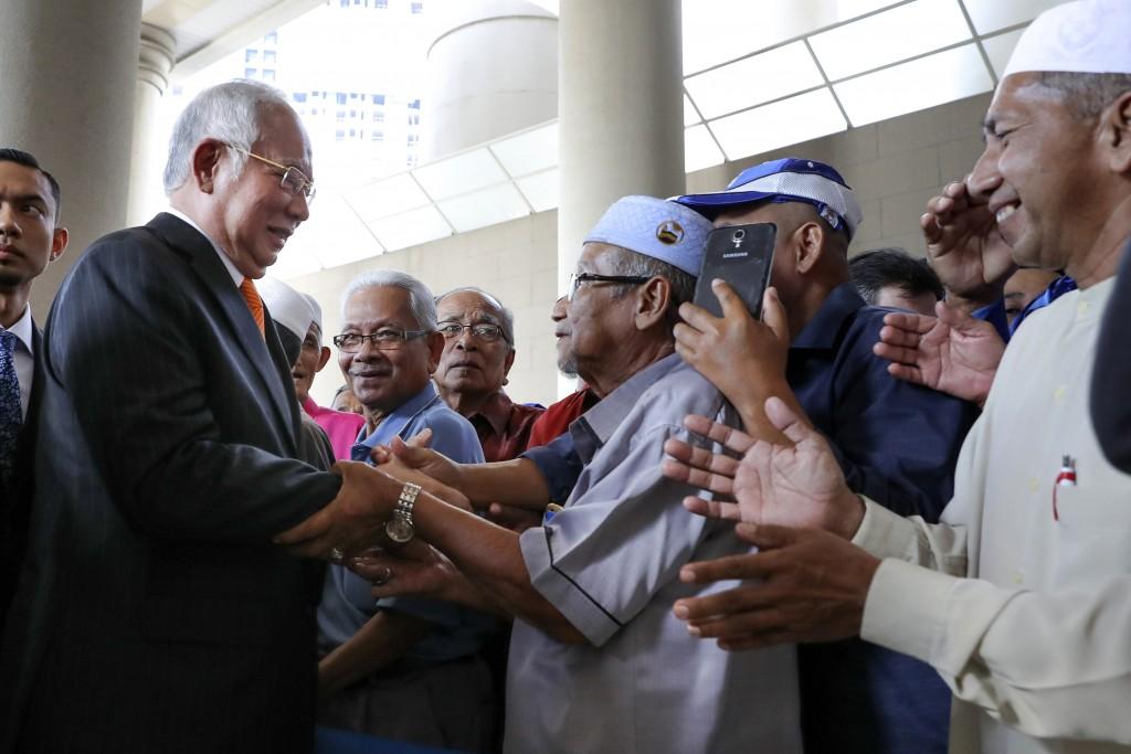Former Malaysian Prime Minister Najib Razak, left, greets supporters as he arrives at Kuala Lumpur High Court in Kuala Lumpur, Malaysia, Monday, Nov. ...