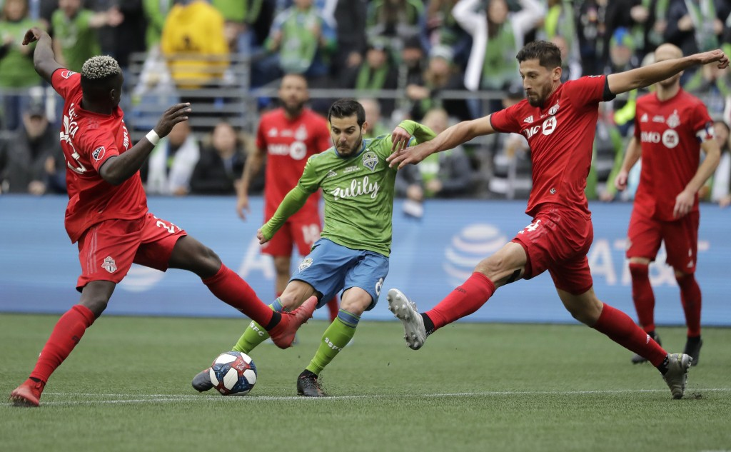 Seattle Sounders' Victor Rodriguez, center, kicks the ball to score between Toronto FC's Chris Mavinga, left, and Omar Gonzalez, Sunday, Nov. 10, 2019...