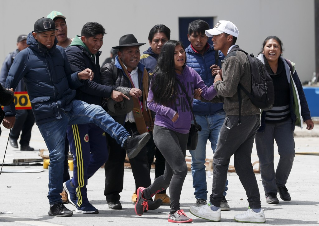 One person that is part of a group of followers of President Evo Morales kicks towards a couple in La Paz, Bolivia, Sunday, Nov. 10, 2019. President E...