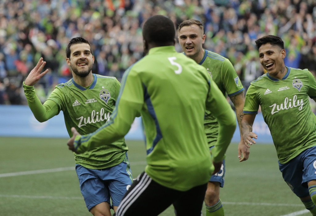 Seattle Sounders' Victor Rodriguez, left, celebrates with teammates after scoring against the Toronto FC, Sunday, Nov. 10, 2019, during the second hal...