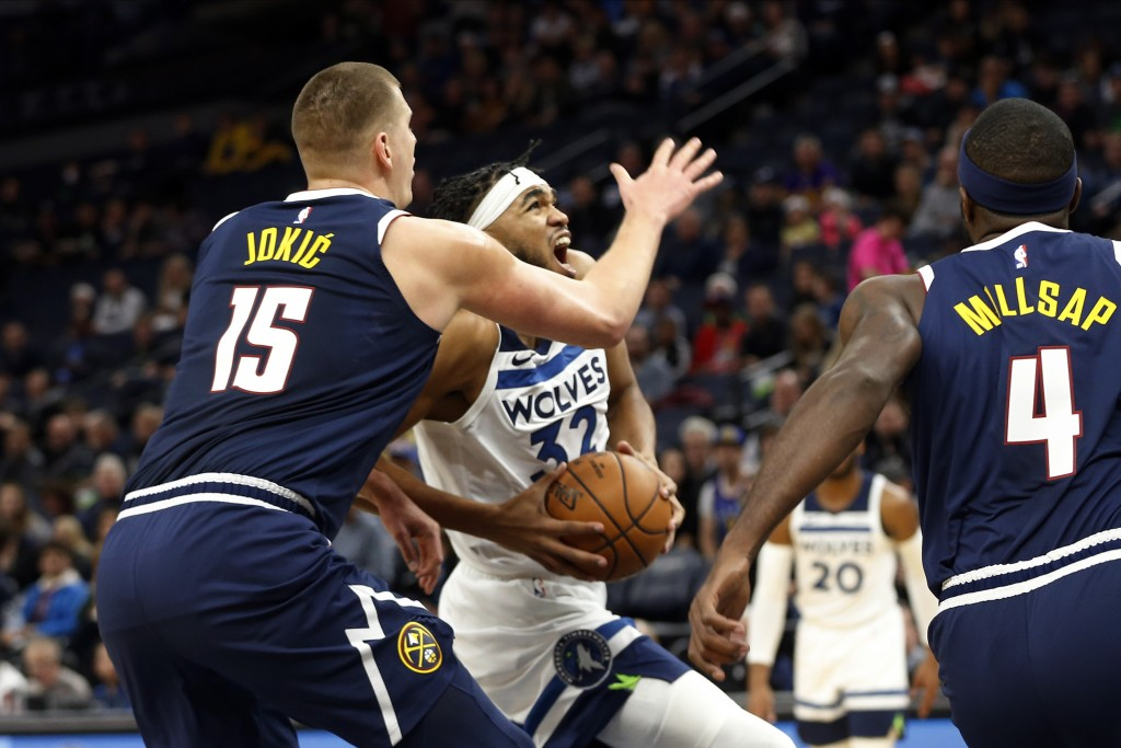 Minnesota Timberwolves' Karl-Anthony Towns , center, drives past Denver Nuggets' Nikola Jokic (15), of Serbia, in the first half of an NBA basketball ...