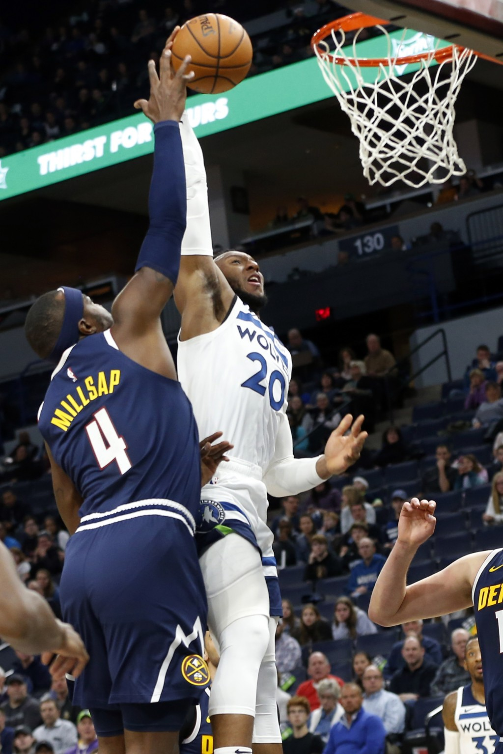 Minnesota Timberwolves' Josh Okogie, right, outreaches Denver Nuggets' Paul Millsap as he goes up for a shot during the first half of an NBA basketbal...