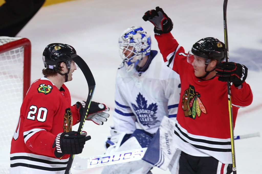 Chicago Blackhawks' Brandon Saad, left, celebrates his goal on Toronto Maple Leafs' Michael Hutchinson, center, with Drake Caggiula during the third p...