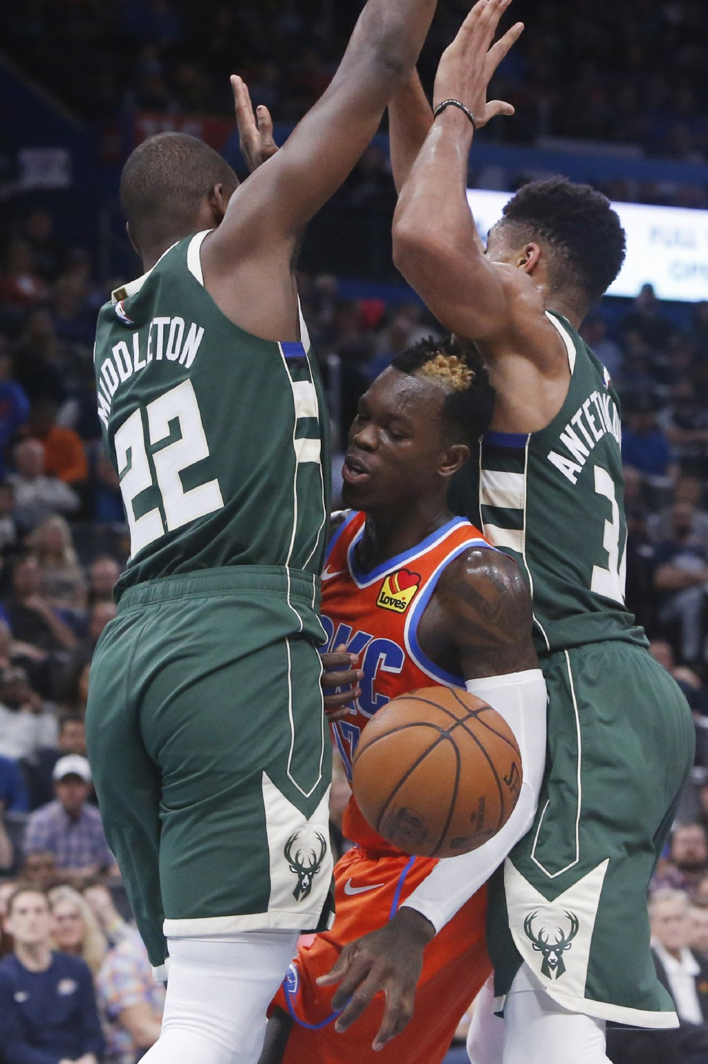 Oklahoma City Thunder guard Dennis Schroeder, center, loses the ball as he is defended by Milwaukee Bucks forwards Khris Middleton (22) and Giannis An...
