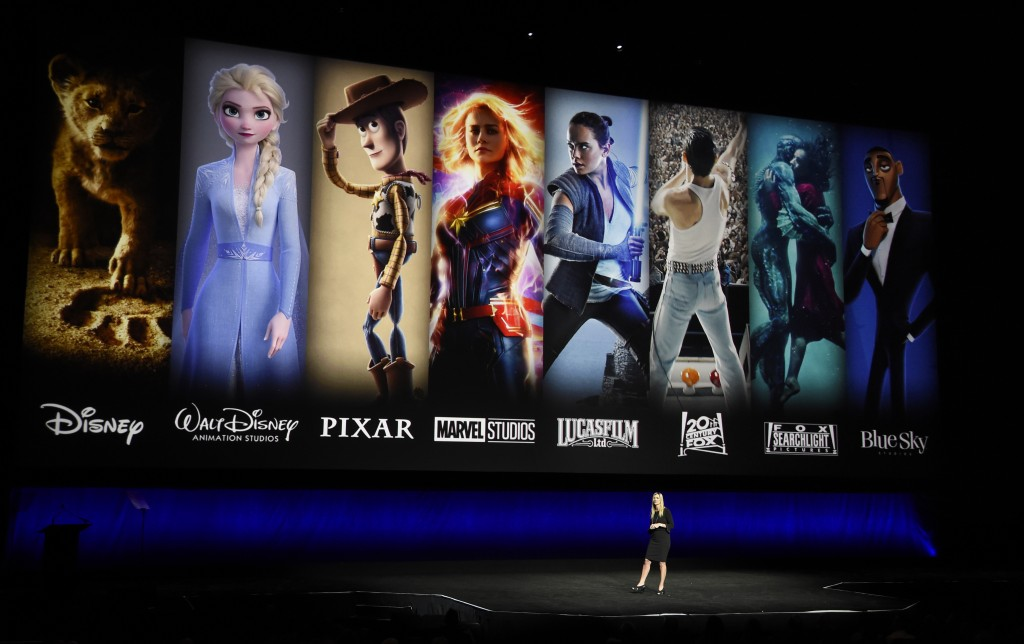FILE - In this April 3, 2019, file photo characters from Disney and Fox movies are displayed behind Cathleen Taff, president of distribution, franchis...