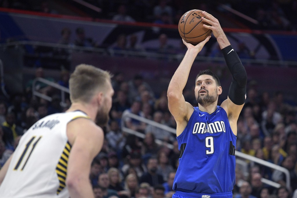 Orlando Magic center Nikola Vucevic (9) shoots in front of Indiana Pacers forward Domantas Sabonis (11) during the second half of an NBA basketball ga...