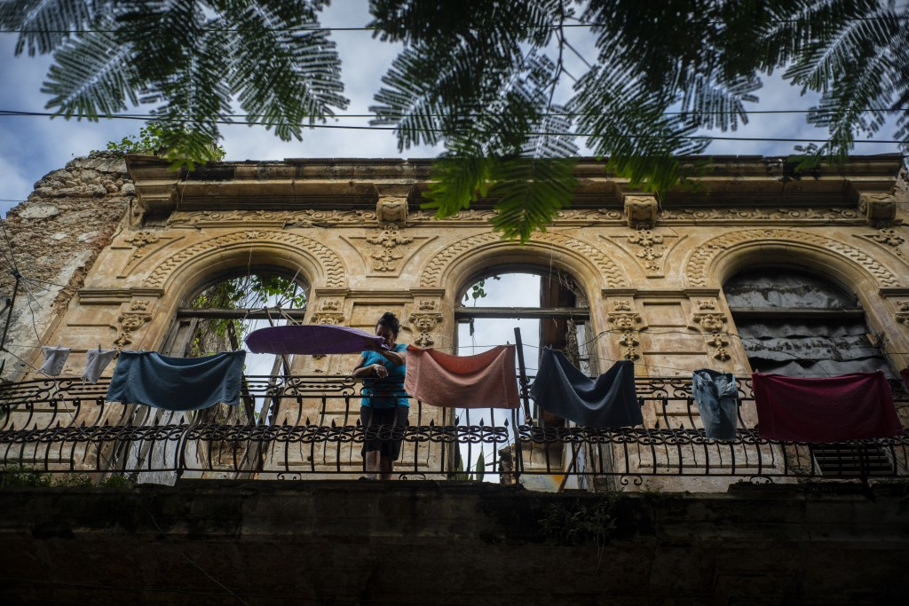In this Nov. 10, 2019 photo, a woman pulls towels off the line after they dried on the balcony of an old home, missing part of its roof, in Havana, Cu...