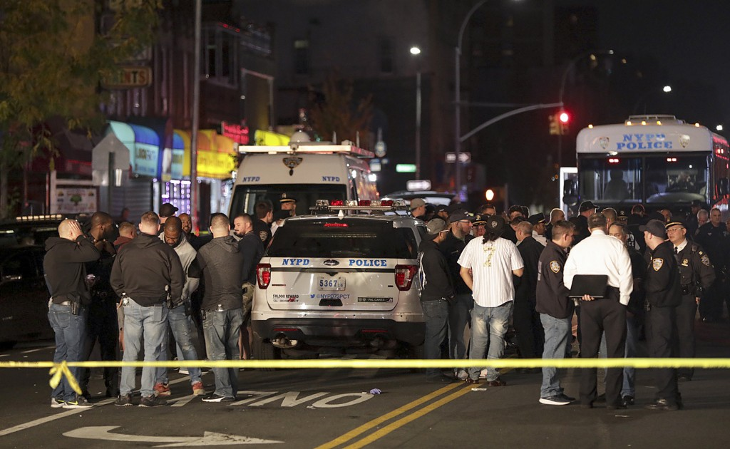 FILE - In this Oct. 25, 2019 file photo, New York police and other emergency personnel investigate the scene of a shooting at a nail salon in the Brow...