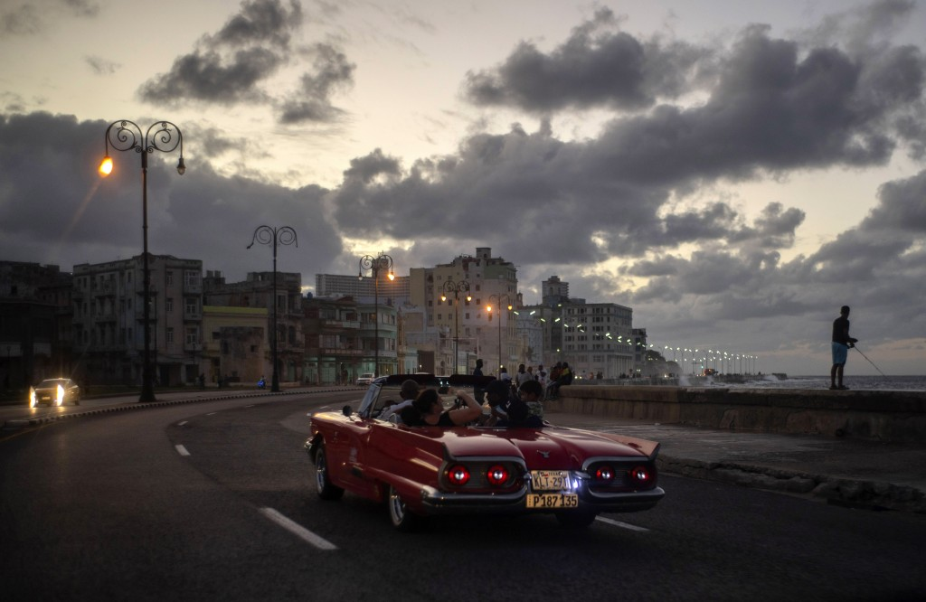 In this Nov. 10, 2019 photo, tourists take a joy ride along the malecon sea wall in Havana, Cuba. The city of Havana will celebrate its 500th annivers...