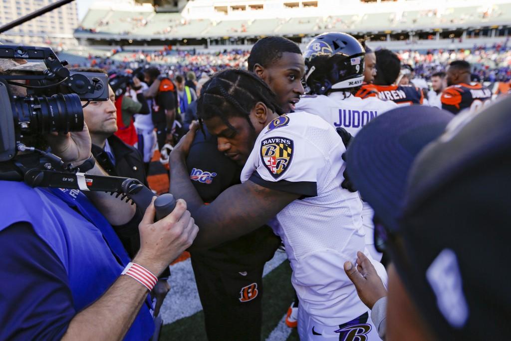 Baltimore Ravens quarterback Lamar Jackson (8), center right, hugs Cincinnati Bengals wide receiver A.J. Green, center left, after an NFL football gam...