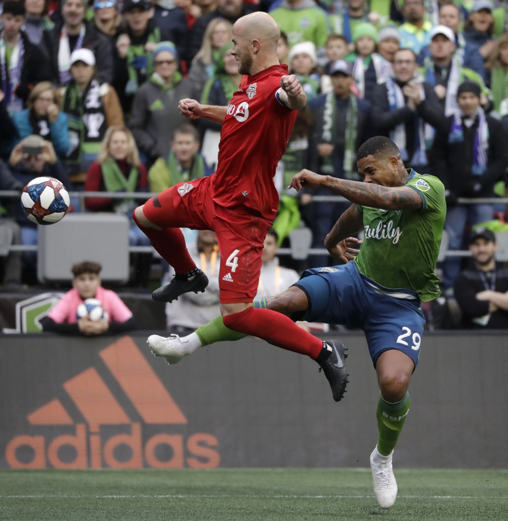Toronto FC's Michael Bradley, left, and Seattle Sounders' Roman Torres battle for the ball Sunday, Nov. 10, 2019, during the first half of the MLS Cup...