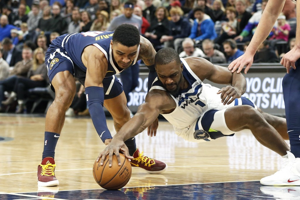 Denver Nuggets' Gary Harris, left, and Minnesota Timberwolves' Noah Vonleh vie for the ball during the first half of an NBA basketball game Sunday, No...