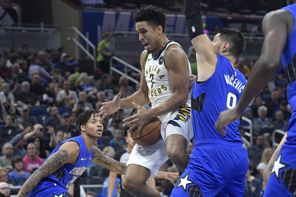Indiana Pacers guard Malcolm Brogdon (7) loses control of the ball while going up to shoot between Orlando Magic guard Markelle Fultz (20) and center ...