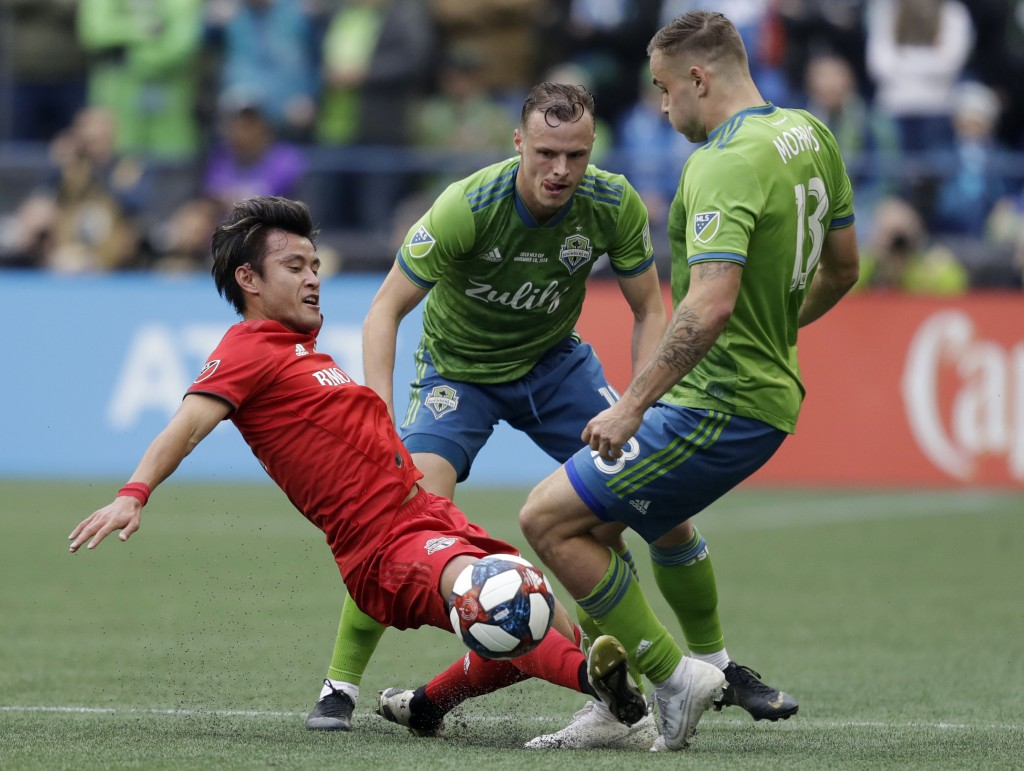 Toronto FC's Tsubasa Endoh, left, battles for a ball with Seattle Sounders' Jordan Morris, right, Sunday, Nov. 10, 2019, during the first half of the ...