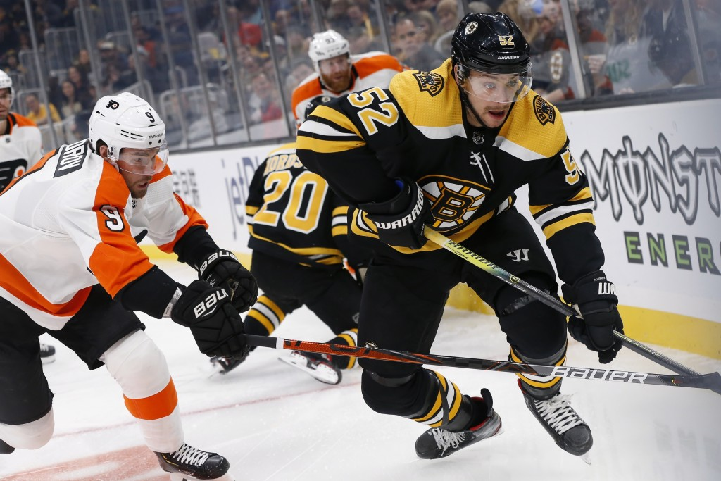 Philadelphia Flyers' Ivan Provorov (9) defends against Boston Bruins' Sean Kuraly (52) during the first period of an NHL hockey game in Boston, Sunday...