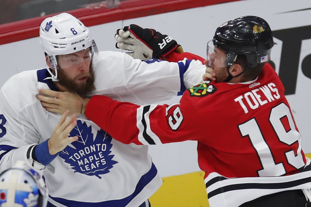 Chicago Blackhawks' Jonathan Toews, right, and Toronto Maple Leafs' Jake Muzzin scuffle during the first period of an NHL hockey game Sunday, Nov. 10,...