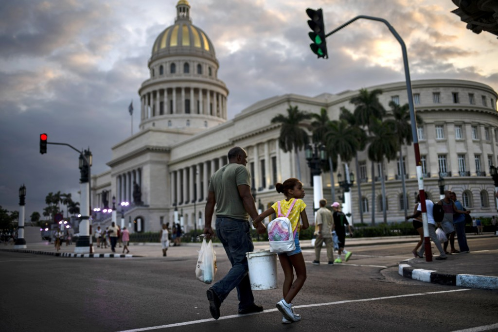 In this Nov 8, 2019 photo, people walk next to the Capital building, with its dome recently restored by Russian specialists in Havana, Cuba. The city ...