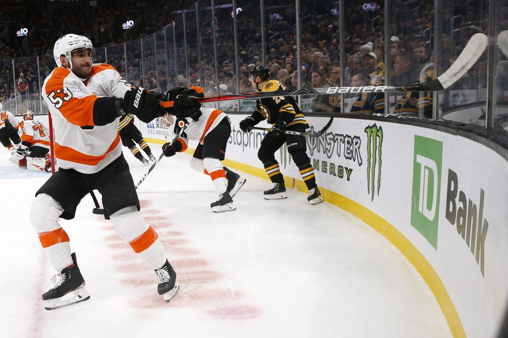 Philadelphia Flyers' Shayne Gostisbehere (53) tries to dislodge his stick after it became wedged in a joint in the glass during the first period of th...