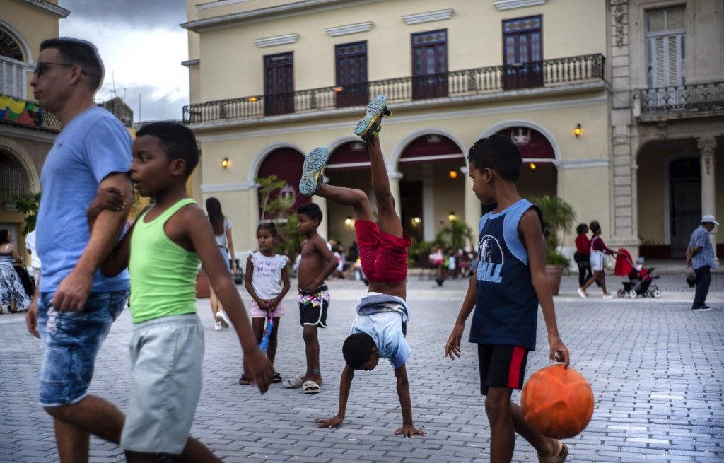 In this Nov. 10, 2019 photo, a youth does hand stands amid pedestrians in a square in Old Havana, Cuba. The city will celebrate its 500th anniversary ...