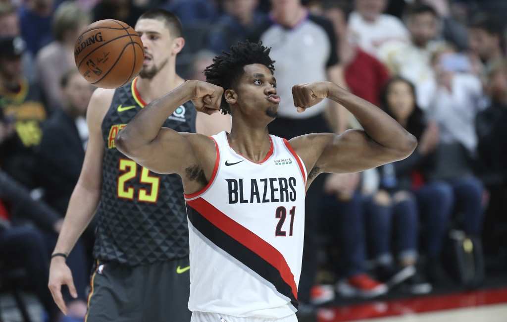 Portland Trail Blazers center Hassan Whiteside, right, flexes after making a basket over Atlanta Hawks center Alex Len during the first half of an NBA...